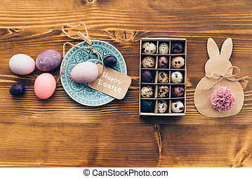 Easter vibes Top view of colored Ester eggs on plate and...