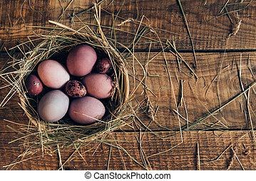 Ester nest Top view of colored Easter eggs in bowl with hay...