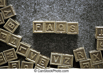 FAQs word made from metallic blocks on blackboard surface