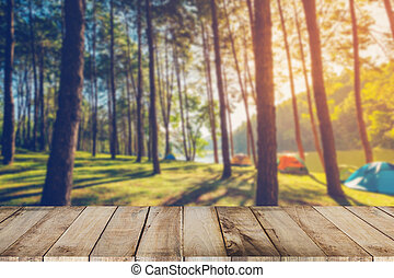 Abstract blurred pine tree and wood table with sunlight...