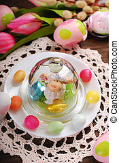 easter table decoration with cute lamb figurine in glass...