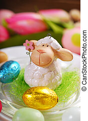 easter table decoration with cute lamb figurine and candy...