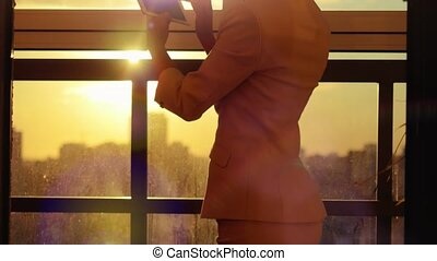 woman using tablet with sunbeams and lens flare Business girl young adult against sunset sky window on blurred city background.