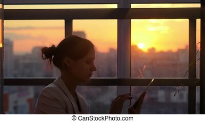 woman using tablet with sunbeams and lens flare Business...