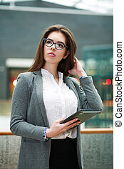 Pensive young business woman holding tablet computer -...