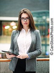 Confident young business woman holding tablet computer -...