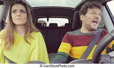 Woman laughing after slapping in face boyfriend while driving car