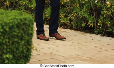 Handsome groom in stylish shoes walking the dog on sunny green alley in Montenegro, Budva close up