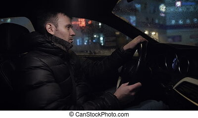Driving a car at night -man driving his modern car at night...