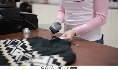 Seller checks the price at the cash register in a clothes...