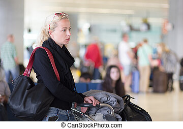 Female traveler using cell phone while waiting - Casual...
