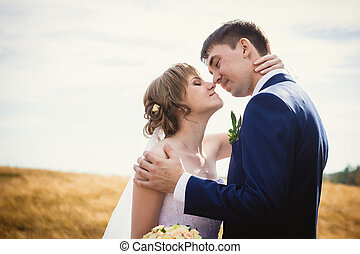 young bride and groom on the background of field