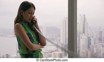1 Young Latina Businesswoman With Wired Telephone In Modern...