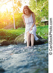 Young woman in the white dress is sitting on the stone in the middle of a creek.