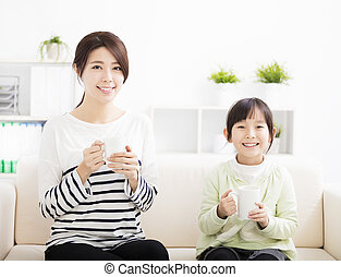 smiling mother and daughter on the sofa
