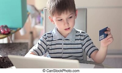 Cute little boy use laptop and credit card - Cute little boy...