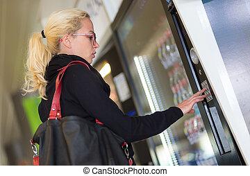 Lady using a modern vending machine - Casual caucasian woman...
