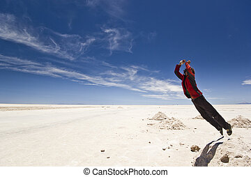 young man jumping from salt heap at Salar Uyuni, Bolivia -...
