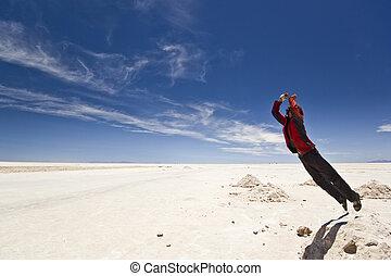 young man jumping from salt heap at Salar Uyuni, Bolivia -...
