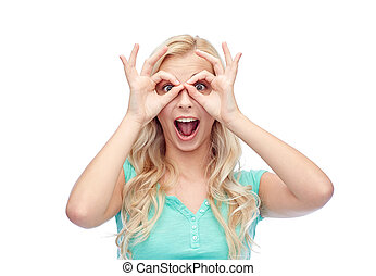 young woman looking through finger glasses - fun, emotions,...