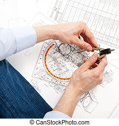 Engineering - An engineer checking a technical drawing with...