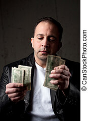 Man Counting His Money - A middle aged man counting a...