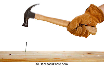 A gloved hand hammering a nail - A leather gloved hammering...