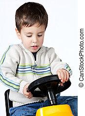 Boy driving a toy car