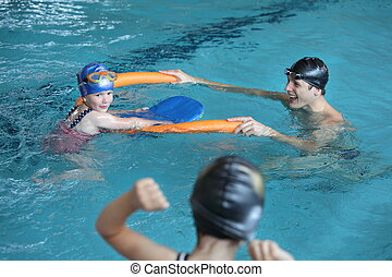 family in swimming pool - father playing with daughters in...