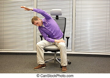 man exercising on chair in office, healthy lifestyle - front...