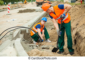 Road construction workers - Construction worker installing...