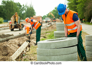 Construction of a manhole - Young worker holding heavy...