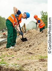Man digging at road construction - Construction worker using...