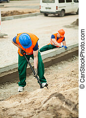 Road under construction - Two workers working hard at road...