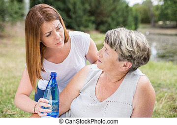 Giving a cold water - Woman is giving her mother a cold...