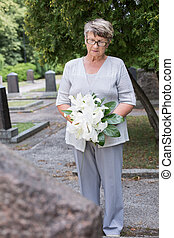 Holding a floral tribute - Elder lady is holding a floral...