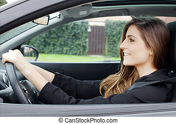 Gorgeous young woman with long hair sitting in car driving smiling happy