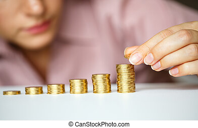 Woman stacking gold coins into increasing columns - Saving,...