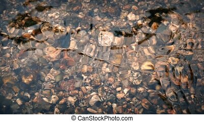 River Bed Through Glassy Water - Rocks on river bottom seen...