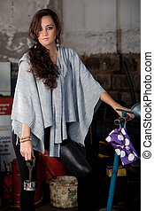 Fashion shot in auto repair shop. - A young brazilian female...