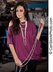 Fashion shot in auto repair shop. - A young brazilian female...