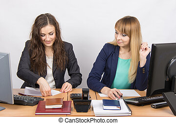 Two young women working in the office, one puts a piece of...