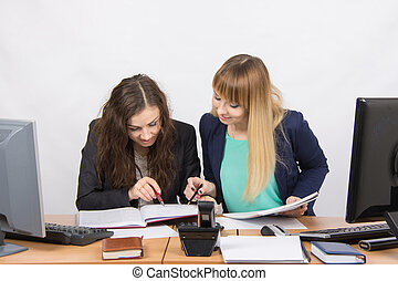 Two girls are looking for colleagues sitting together the...