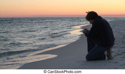 Kneeling Prayer At Sunset - Woman kneels in prayer at the...