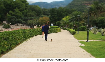 Handsome groom running with the dog on sunny alley in Montenegro, Budva (back view)