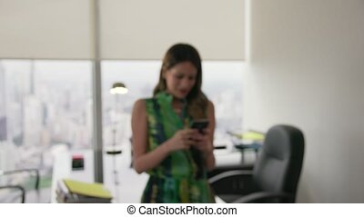 11 Young Latina Woman Text Messaging On Phone In Office -...