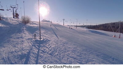 View of the ski slope covered with snow on a bright sunny...