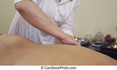 Close up of masseuse hands pinch a back of adult fat man...