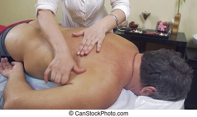 Masseuse rubdown lower back of adult fat man. Therapeutic...