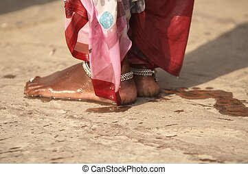 Wet Feet - Feet of a woman in red and pink sari standing on...
